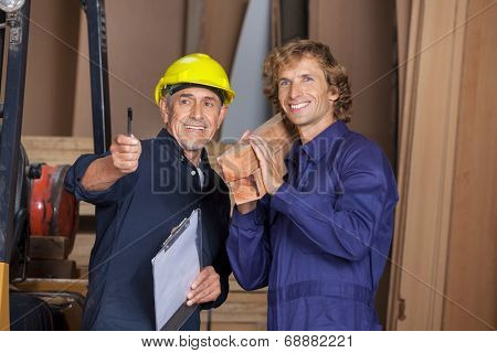 Happy male carpenter showing something to coworker carrying wooden planks in workshop