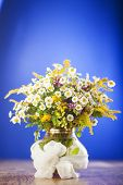 Wildflowers bouquet in glass vase on blue background poster