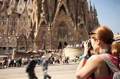 Young woman taking picture of Sagrada Familia. On April 16, 2014 in Barcelona, Spain. poster