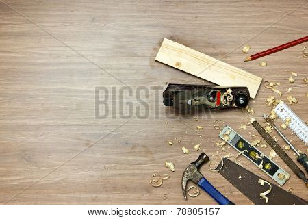 Wood working tools, used in carpentry by a carpenter background. Assorted items, such as a hammer, a wood saw, a spirit level, rasp, screw driver, a carpenter's square and pencil,