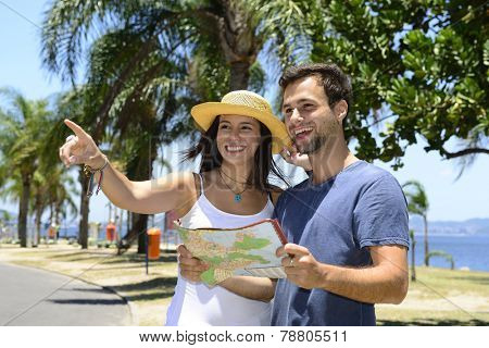 Happy tourist couple with map pointing at destination