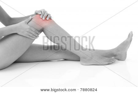 Woman holding on sore knee isolated on white. poster