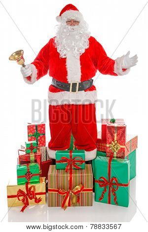 Father Christmas or Santa Claus holding a gold bell surrounded by piles of gift wrapped presents, isolated on a white background.