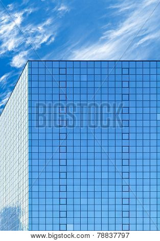 Modern Office Building Made Of Blue Glass And Cloudy Sky