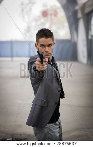 Well dressed handsome young detective or policeman or mobster standing in an urban environment aiming a firearm directly to the camera with a determined expression front view poster