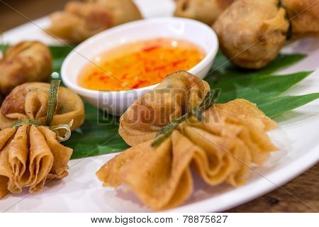 Oriental fried wonton filled with prawns and vegetables served with sweet chilli and dumpling sauce. poster