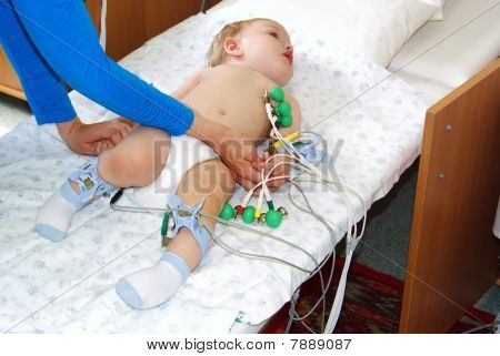 The little child with tear-stained eyes lays on a couch in hospital and to it do the heart cardiogramme poster