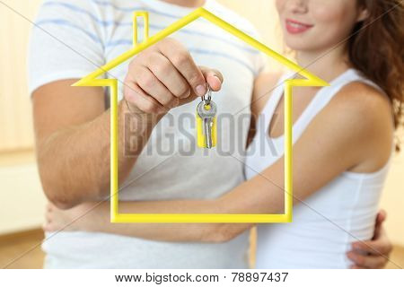 Young couple with keys surrounded by form of house
