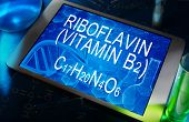 the chemical formula of Riboflavin (vitamin B2) on a tablet with test tubes poster