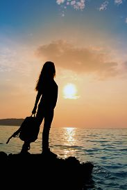 The silhouette of the girl with backpack at sunset