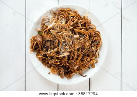 Asian dish stir fried char kuey teow over wooden background.  Fresh cooked with hot steams.