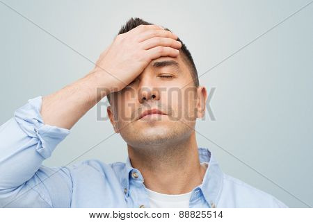 stress, headache, health care and people concept - unhappy man with closed eyes touching his forehead over gray background poster
