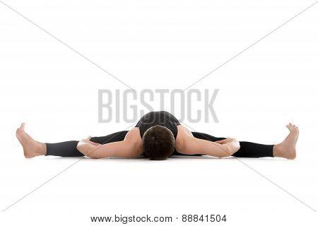 Sporty young man doing splits yoga pilates stretching exercises lying in Upavistha Konasana Wide Angle Seated Forward Bend poster