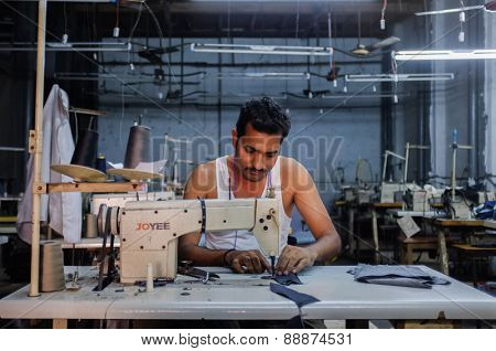MUMBAI, INDIA - 12 JANUARY 2015: Indian worker sowing in a clothing factory in Dharavi slum