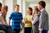 education, elementary school, drinks, children and people concept - group of school kids with soda cans talking in corridor poster