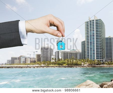 A hand is holding a key from the new home. A concept of real estate property agency. Miami cityscape on the background. poster