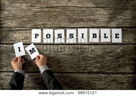 Businessman Taking Away Letters Im From The Word Impossible Spelled On Individual White Cards Lying