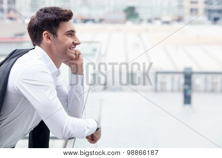 Handsome young businessman is using phone for communication