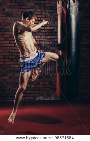 muscular handsome fighter giving a forceful forward kick during  practise round with  boxing bag, ki