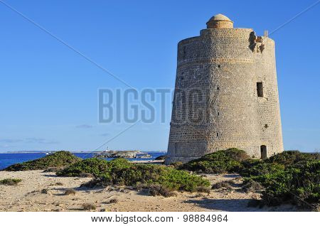 a view of the medieval tower Torre de Ses Portes in Ibiza Island, Spain, and the neighboring Formentera Island in the background