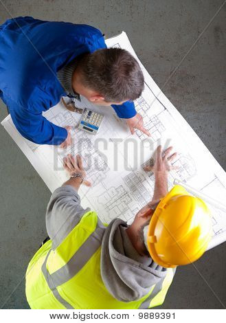 Two Builders Discuss Construction Blueprints
