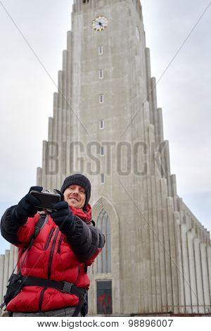 Happy Caucasian man taking selfie in front of the Hallgrimskirkja cathedral in Reykjavik Iceland