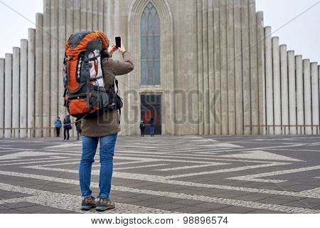 rear view of tourist woman standing in front of the Hallgrimskirkja cathedral in reykjavik iceland, taking pictures with cell phone