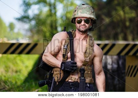 Powerful mercenary with submachine gun guarding a roadblock. Cropped portrait of strong ripped man in helmet and sunglasses with rifle in hand. Soldier mercenary warrior paintball military concept