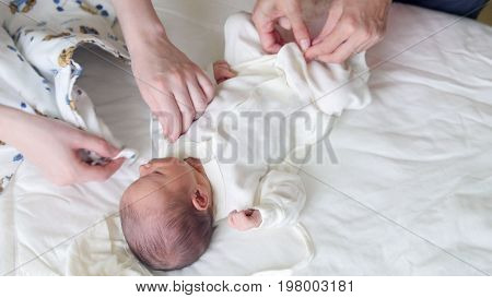 Newborn baby, mother and nurse - swaddling the infant, close up