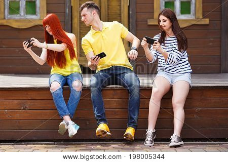 Group Of Three Friends Play Mobile Video Game Outdoors, Prying O