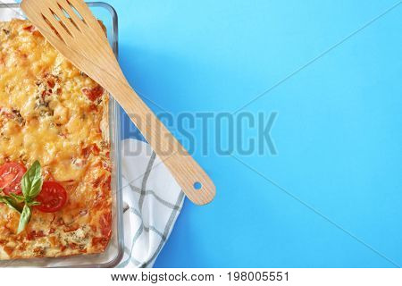 Baking tray with delicious turkey casserole and wooden spatula on color background