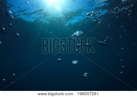 Air bubbles underwater in blue water