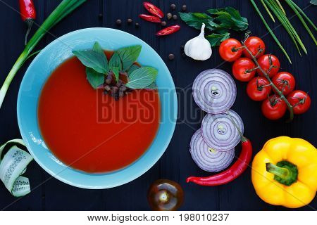Spanish Soup Gazpacho With Basil Leaves In Blue Plate On Black T