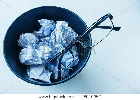 Glasses thrown in a bucket of garbage. Concept vision recovery vision correction.