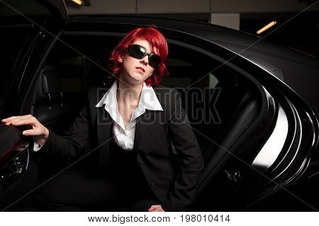 pretty mafia chick getting out of the car, wearing huge sunglasses