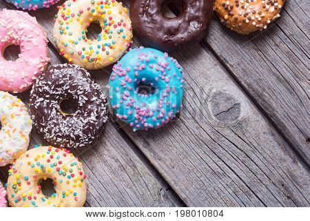 assorted donuts with chocolate frosted pink glazed and sprinkles .