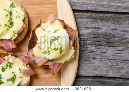 Eggs benedict with bacon on wooden background . Top view . Space for text