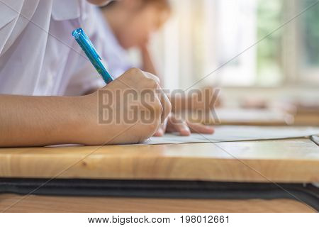 Students using pen writing information on white answer paper in high school Asian exams room Tests or examination is assessment intended to measure knowledge skill aptitude Education Concept