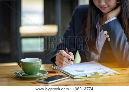 Businesswomen Are Writing And Reading Reports On Banking And Finance.