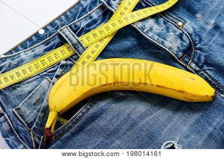 Mens denim pants with banana imitating male genitals. Kinky fruit on denim fabric close up. Health and male sexuality concept. Blue jeans with measure tape instead of belt on white background.