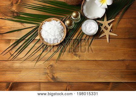 Spa composition with body care products and coconut on wooden background