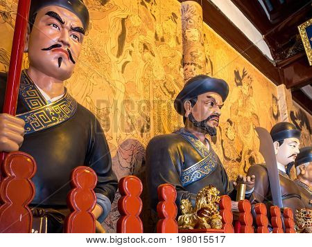 Shanghai, China - Nov 6, 2016: Inside the 600-year-old Old City God Temple. Statues of gigantic Taoist guards stand along the wall. Low-light image.