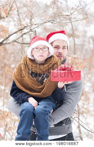 small boy in glasses santa claus hat and knitted scarf and handsome man or bearded father guy holds red christmas or new year present box in winter outdoor with snow on natural background