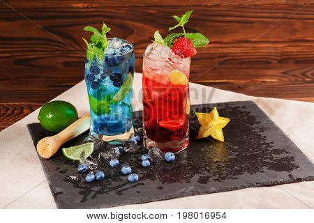 Close-up of blue and red drinks on black table-napkin. Tasty bright summer cocktails with mint twigs blueberries strawberries ice and carambola in highball glasses on the wooden background.