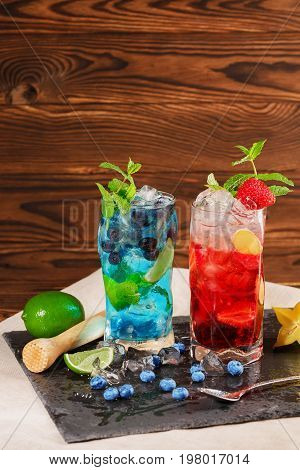 Close-up picture of blue and red drinks on black desk. Two alcohol summer cocktails with mint twigs blueberries strawberries ice and carambola in highball glasses on the wooden background.