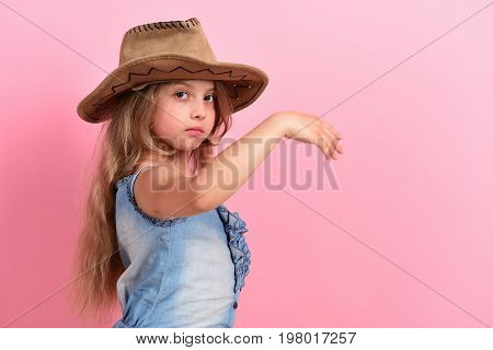 Kid with serious face and long fair hair wears jeans dress. Fashion and casual style concept. Girl in fancy outfit wears cowboy hat. Little lady in stylish clothes on pink background copy space