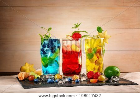 Close-up picture of blue yellow and red drinks on black desk. Tasty bright summer cocktails with mint blueberries strawberries grapes ice and carambola in highball glasses on a wooden background.