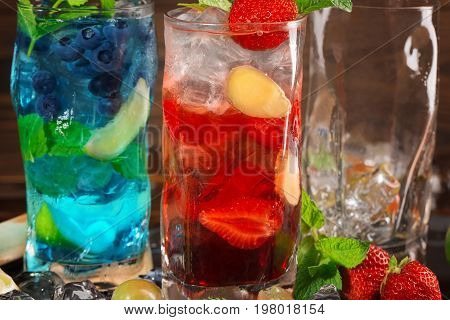 Close-up picture of blue and red drinks. Two tasty bright summer cocktails with mint leaves cut strawberries ginger and ice cubes in highball transparent cocktail glasses. Cocktails for parties.