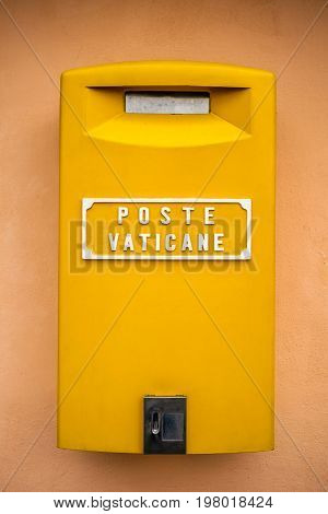 Yellow post box on the wall on the wall of a building at Vatican, Rome, Italy.