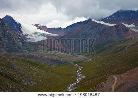 The view from the mountain pass to the peaks glaciers river valley Tien Shan Kyrgyzstan altitude rocks stones road clouds cloudy